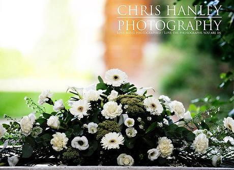 The top table wedding flowers: pure white roses, gerbera daisies, carnations and rich, dark green foliage.