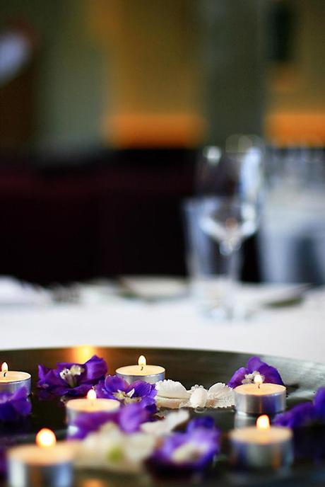 Simple table centrepieces with flowers and tealights - these are really pretty