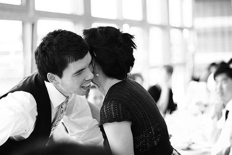 Female guest kissing the groom