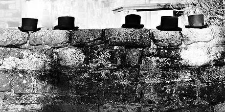 wedding blog photograph of top hats on a stone wall