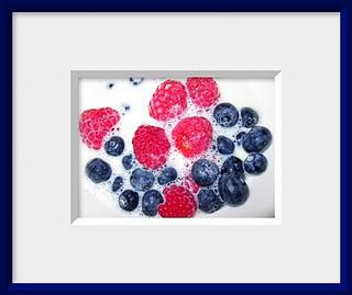A bowl of fresh red raspberries and blueberries splashed with milk makes a healthy breakfast still life.