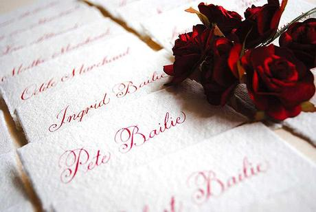 Rustic wedding place cards in red calligraphy