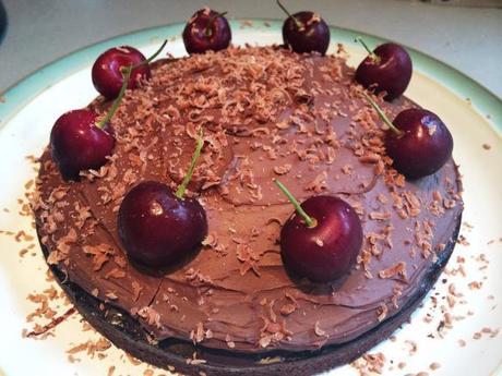 black forest cake chocolate topping with fresh cherries and stalks and grated chocolate
