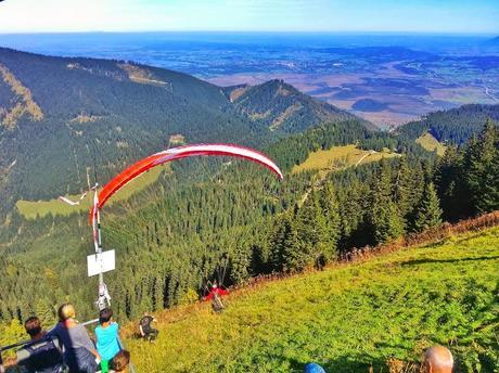 Paraglider taking off from Laber Mountain to sail over the Ammergau Alps.