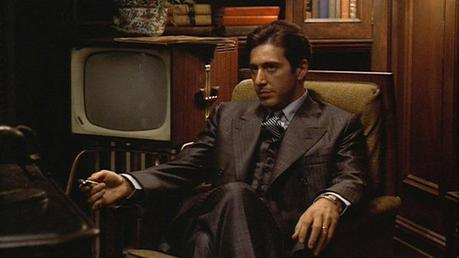 Michael Corleone in his preferred pose: arms relaxed, legs crossed, sitting in an office surrounded by men who will kill for him at the drop of a hat.