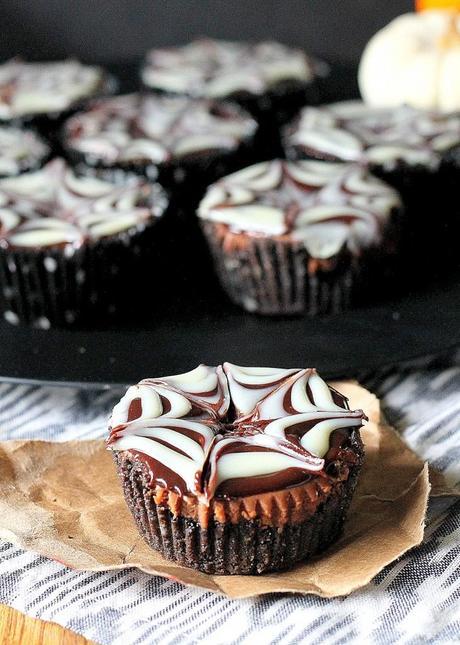 Death by Chocolate Mini Cheesecakes | Dark chocolate cheesecake with mini chocolate chips, an Oreo crust, and a chocolate ganache spiderweb! Recipe from Bakerita.com