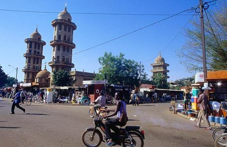 A cyclist putters past market stalls in the bustling Burkina Faso capital Ougadougou, under a bright blue sky.