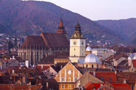 The gothic outline of Brasov's Black Church and silver-domed buildings in Brasov, Romania, in front of the thickly forested Carpathian Mountains.