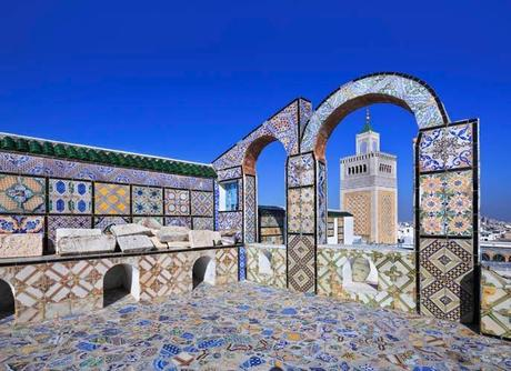 Brightly coloured tiles in blue, yellow and green cover the interior of an open-roofed mosque building in Tunisia.