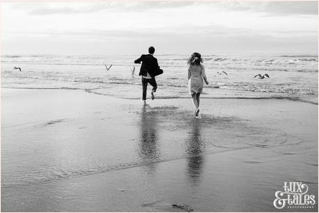 Photography Engagement Shoot in Whitby | Girl wearing Red Flower crown | Alterntive Couple whereing Vintage clothing | Running into the ocean burds scatter