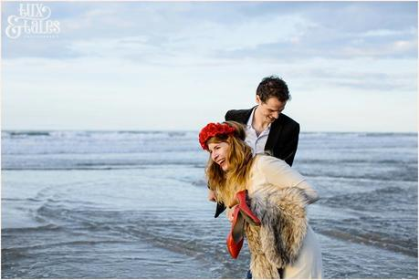 Photography Engagement Shoot in Whitby | Girl wearing Red Flower crown | Alterntive Couple whereing Vintage clothing | Couple laughing at beach