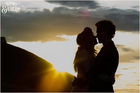 Photography Engagement Shoot in Whitby | Girl wearing Red Flower crown | Alterntive Couple whereing Vintage clothing | Silhouette in the sunset at the beach