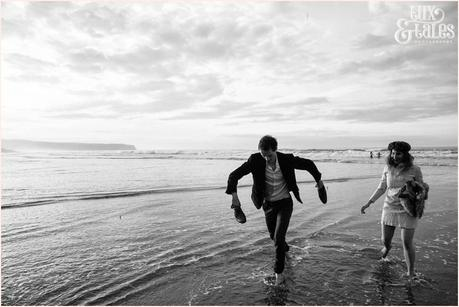 Photography Engagement Shoot in Whitby | Girl wearing Red Flower crown | Alterntive Couple whereing Vintage clothing | Running in the ocean man holding shoes