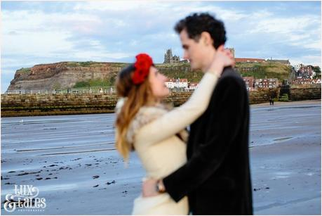 Photography Engagement Shoot in Whitby | Girl wearing Red Flower crown | Alterntive Couple whereing Vintage clothing | Hugging with whitby abbey in the background