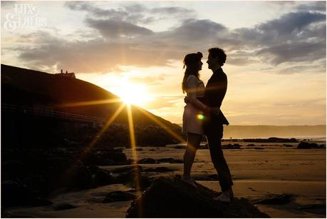 Photography Engagement Shoot in Whitby | Girl wearing Red Flower crown | Alterntive Couple whereing Vintage clothing | Beach silhouette with the sunset with starburst