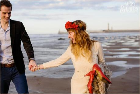 Photography Engagement Shoot in Whitby | Girl wearing Red Flower crown | Alterntive Couple whereing Vintage clothing | Holding hands on beach