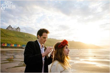 Photography Engagement Shoot in Whitby | Girl wearing Red Flower crown | Alterntive Couple whereing Vintage clothing | Man ties flower crown