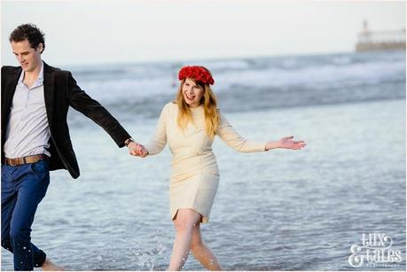 Photography Engagement Shoot in Whitby | Girl wearing Red Flower crown | Alterntive Couple whereing Vintage clothing | Being silly on the beach
