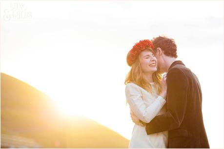 Photography Engagement Shoot in Whitby | Girl wearing Red Flower crown | Alterntive Couple whereing Vintage clothing | Hugging and cuddling in the sunset