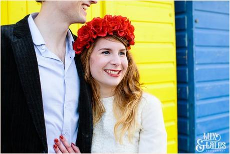 Photography Engagement Shoot in Whitby | Girl wearing Red Flower crown | Alterntive Couple whereing Vintage clothing | Hugging in front of the rainbow coloured bach huts