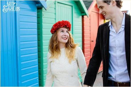Photography Engagement Shoot in Whitby | Girl wearing Red Flower crown | Alterntive Couple whereing Vintage clothing | Rainbow coloured beach huts