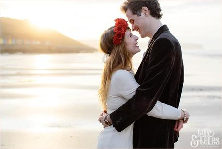 Photography Engagement Shoot in Whitby | Girl wearing Red Flower crown | Alterntive Couple whereing Vintage clothing | couple hugging in the sunset