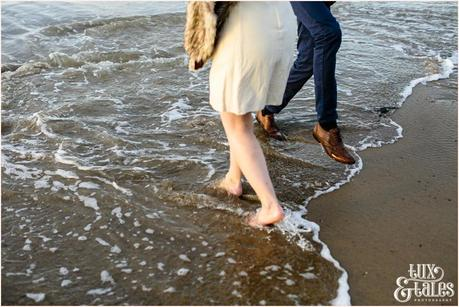 Photography Engagement Shoot in Whitby | Girl wearing Red Flower crown | Alterntive Couple whereing Vintage clothing | walking in water at beach
