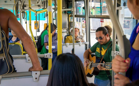 A man relieving some of the morning transit stress with his guitar