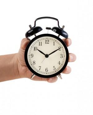 Hand holding Retro style alarm clock, isolated on white
