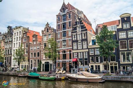 houses along a canal in Amsterdam with boats in the canal