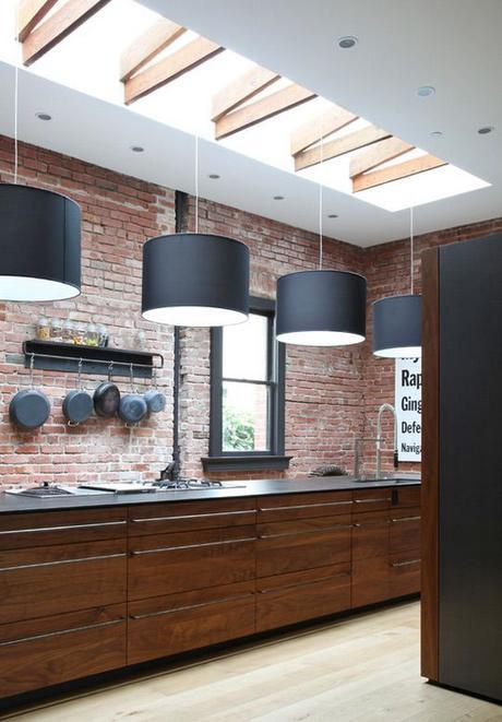 Industrial warehouse look kitchen with exposed red brick and sunlight with wooden beams. Love the hanging iron pans - adds so much character!