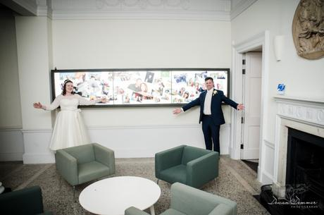 Bride and Groom in front of panel of their pictures