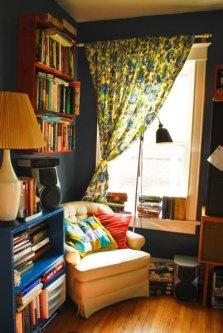 Living Room Corner Reading Nook Dark Gray Walls Yellow Chair Cluttered Cozy Floral Curtains Interior Decor