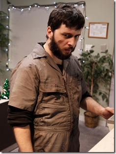 Coveralls (Neal Starbird) examines the printer in The Ruckus Theater's