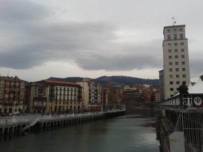Bilbao is built by a river and with mountains in behind.