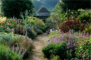 Parham. Sussex. Cool color borders in summer. Path with view through to dovecote