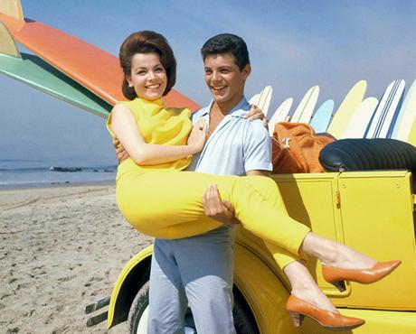 Frankie Avalon holding Annette Funicello on beach next to dune buggy with surfboards, sand ocean in background