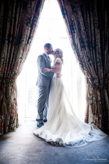 bride-and-groom-kiss-by-window
