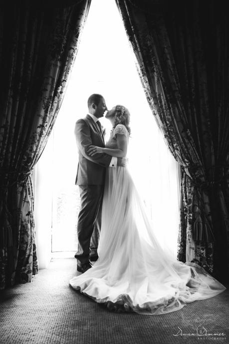 bride-and-greoom-posed-by-window-black-and-white