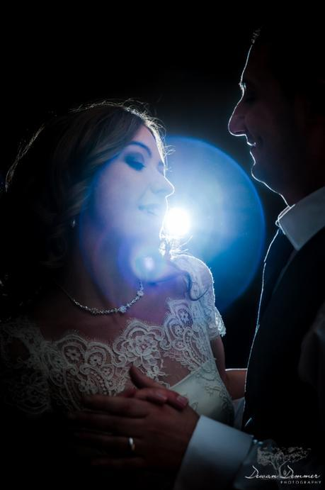 Bride and groom dance with light behind