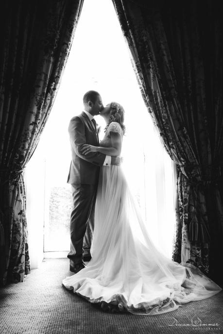 BW Bride and groom kiss at window