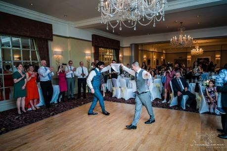Groom and brother greek dancing at wedding