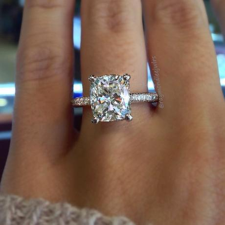 Cushion Cut solitaire engagement ring on thin diamond band.