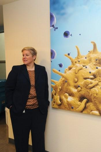 StemExpress founder-CEO Cate Dyer stands next to photo of a stem cell
