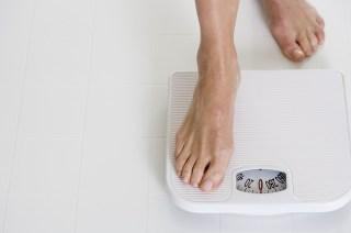 Woman Stepping onto Scale --- Image by © Royalty-Free/Corbis