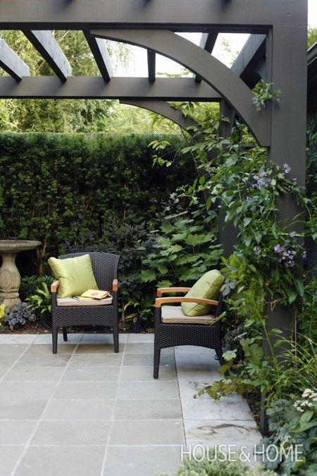House & Home Outdoor room framed with a black painted arbour overhead, black seating and bluestone floor.