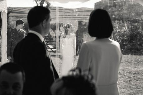 Bride's parents looking through marquee at their daughter