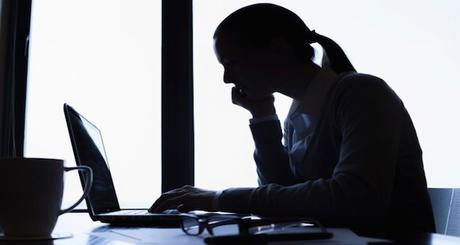 Silhouette of businesswoman using computer