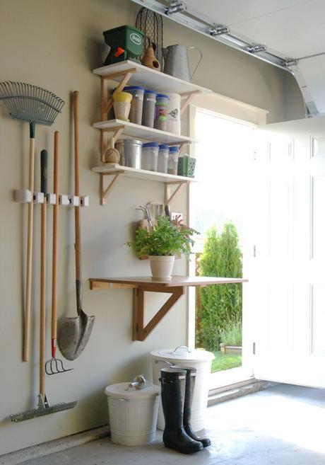 From Mini Manor Blog. I love this organizational station for yard and garden supplies. The table (for potting) folds down so the car can come in. The smaller tools are in the bag begin the fern and the larger tools are hanging. Soil in bigger trash can.: