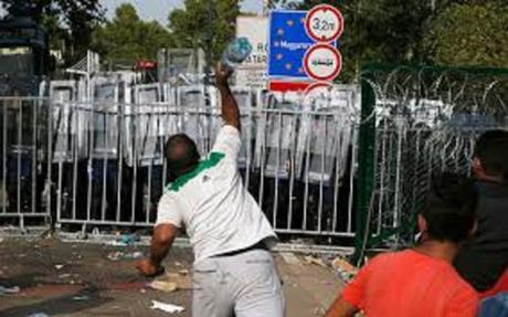 migrant throw bottle at Hungarian riot police at border